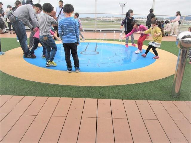 ミニ噴水コーナーで水で遊ぶ子供たち
