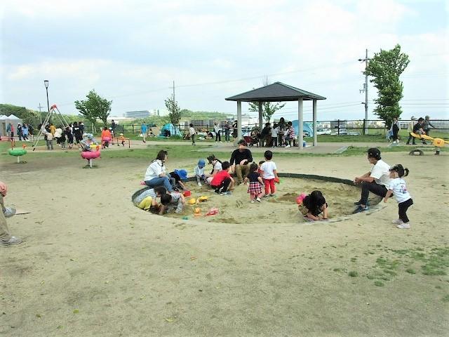 砂場やブランコで遊ぶ家族