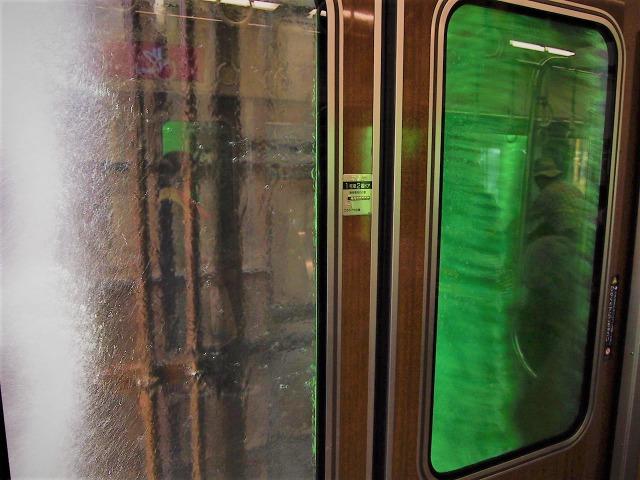 緑色のブラシと強い水圧で洗われていく阪急電車